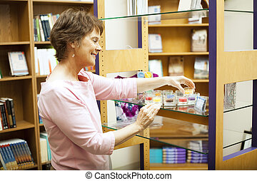 Shop Owner Arranges Display - Store owner arranging a...