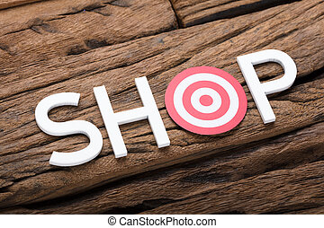Shop Text With Dartboard On Wooden Table