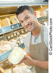 Shop worker holding expensive cheese