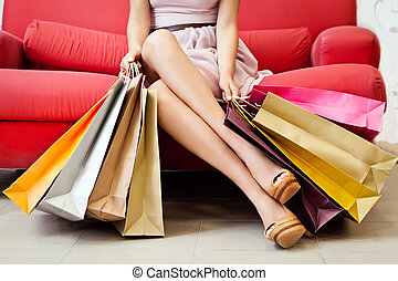 Shopaholic - A woman with many shopping bags.