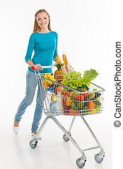 shopaholic., alegre, mulher jovem, carregar, carro shopping, cheio, de, bens, e, sorrindo, enquanto, isolado, branco
