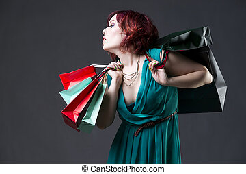 Shopaholic concept, young beautiful red-haired caucasian woman in aquamarine dress