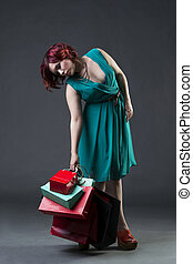 Shopaholic concept, young beautiful red-haired caucasian woman