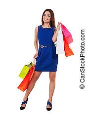 shopaholic, girl., hermoso, mujer joven, en, vestido azul, tenencia, bolsas de compras