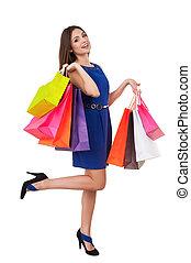 shopaholic, girl., longitud completa, de, hermoso, mujer joven, en, vestido azul, tenencia, bolsas de compras, y, sonriente, en cámara del juez