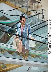 Shopaholic moving up escalator