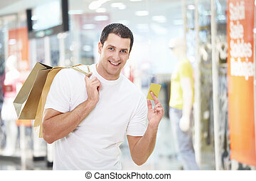 Shopaholic - A young man with the shopping and credit card...