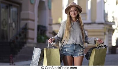 Shopaholic woman holding many shopping bags excited. Blond...