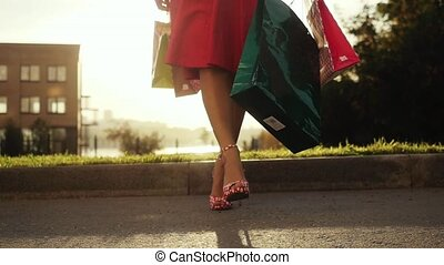Shopaholic woman in beautiful dress holding many shopping bags walking on the street through the sun during sunset in slow motion.