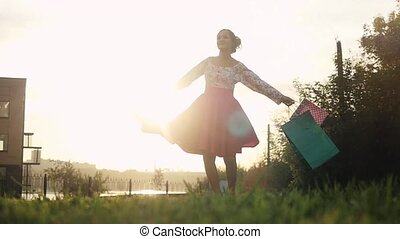 Shopaholic woman in beautiful dress spinning around holding many shopping bags walking on the street through the sun during sunset in slowmotion. 1920x1080