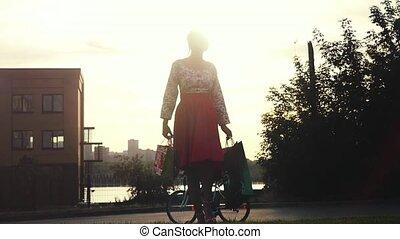 Shopaholic woman in beautiful dress holding many shopping...