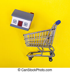 Shoping cart with rubber houses on a yellow background.