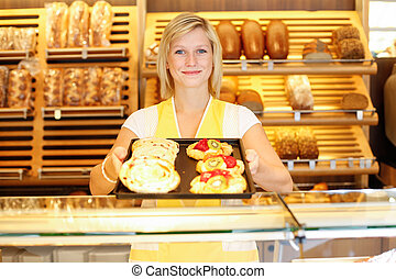 Shopkeeper in baker shop with tablet full of cake - ...
