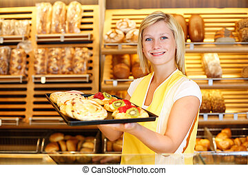 Shopkeeper in baker shop with tablet full of cake -...