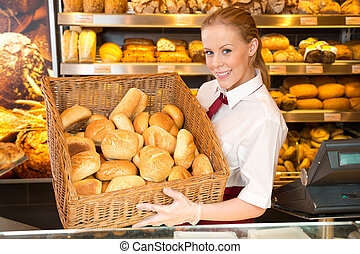 Shopkeeper in baker's shop presenting buns in a basket