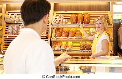 Shopkeeper in baker's shop with customer - Bakery shopkeeper...