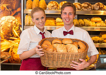 Shopkeepers in baker's shop presenting buns in a basket