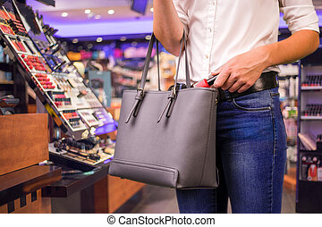 shoplifter at work - Young woman is stealing goods in a shop
