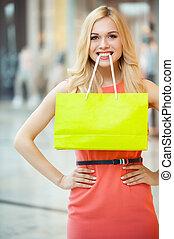 shoppen , is, fun., mooi, jonge vrouw , vasthouden, winkeltas, in, haar, mond, en, het glimlachen