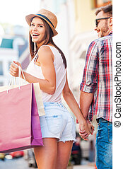 shoppen , samen, is, fun!, achterk bezichtiging, van, mooi, jonge, verliefd koppel, wandelende, door, de, straat, terwijl, mooie vrouw, verdragend, het winkelen zakken, en, het kijken overheen de schouder