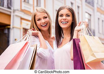 shoppen , samen, is, fun., twee, aantrekkelijk, jonge vrouwen, vasthouden, het winkelen zakken, en, het glimlachen, terwijl, staand, buitenshuis