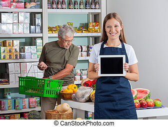 shoppen , tablet, het tonen, terwijl, digitale , verkoopster, hogere mens