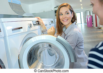 shopper choosing washing machine in household appliance...