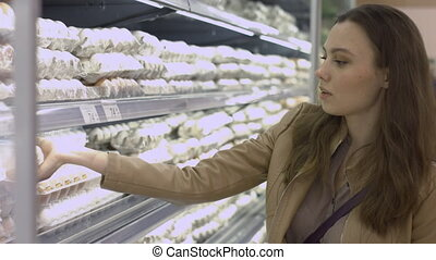 Shopper girl chooses eggs at the supermarket