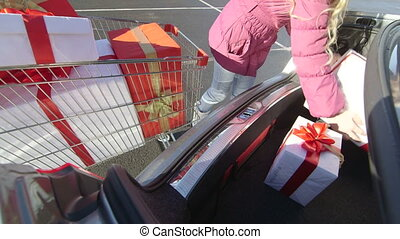 Shopper girl with shopping cart full of gift boxes loads car...