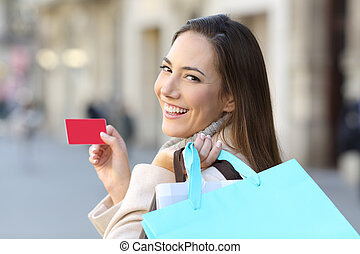Shopper holding shopping bags and credit card