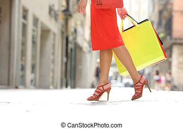 Shopper legs walking with shopping bags