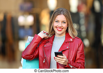 Shopper posing holding a phone and shopping bags