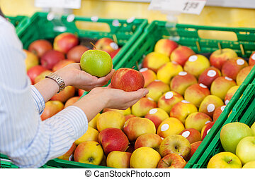 Shopper purchasing apples in a supermarket