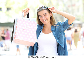 Shopper showing blank shopping bags in the street