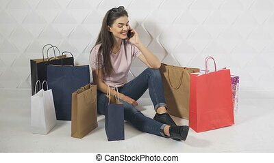Shopper Talks on Phone - Beautiful brunet, surrounded by...