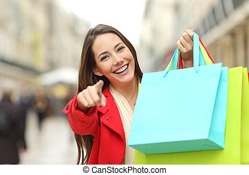 Shopper with shopping bags pointing you