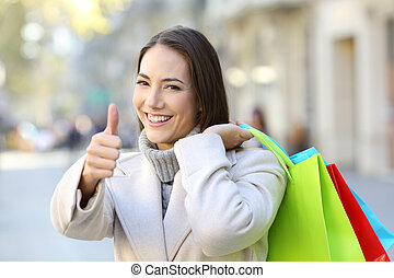 Shopper with thumbs up holding shopping bags in winter