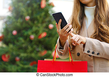 Shopper woman using smart phone for shopping online and carrying bags on Christmas time.