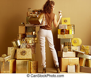 shopper woman with golden laptop and cup of latte macchiato