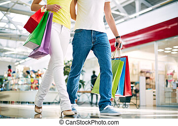 Shoppers in jeans - Legs of young couple going in the mall