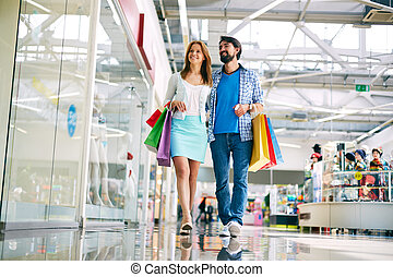 Shoppers in new mall - Casual couple walking in the big mall