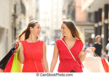 Shoppers talking holding shopping bags