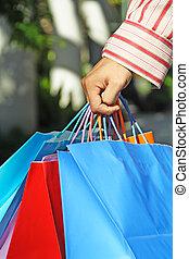A shot of a young man carrying shopping bags