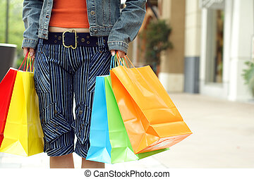 Shopping - A woman shopping in a mall carrying shopping bags