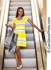 shopping african woman using escalator