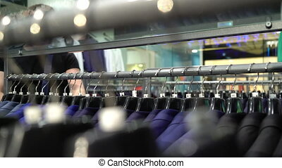 Shopping and fashion concept - Young man choosing and trying...