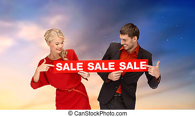 couple with red sale sign