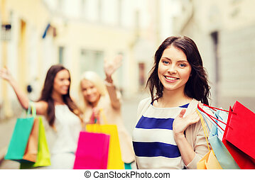 girls with shopping bags in city - shopping and tourism ...