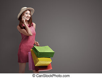 Shopping asian woman talking on the phone and holding bags