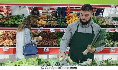 Shopping assistant puts leek on supermarket counter. High ...